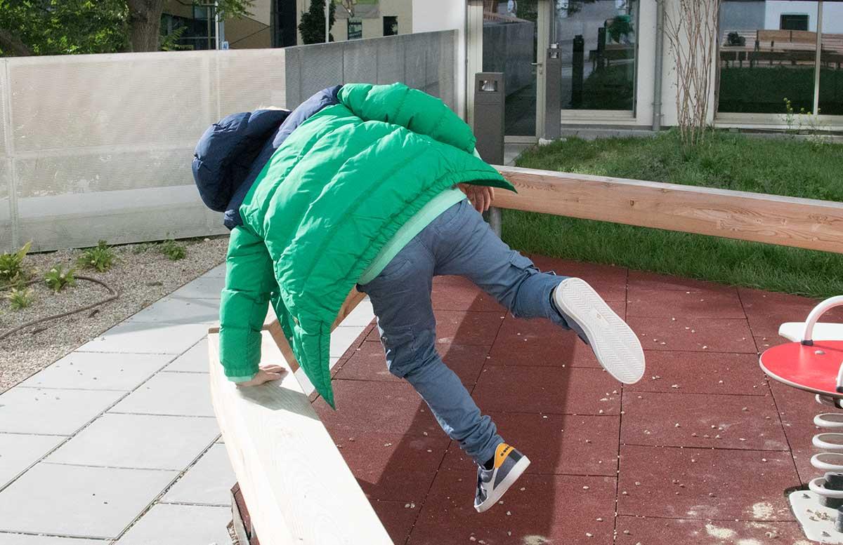 Back to School Herbst Outfit von TK Maxx Lenny mit grüner jacke hüpfend