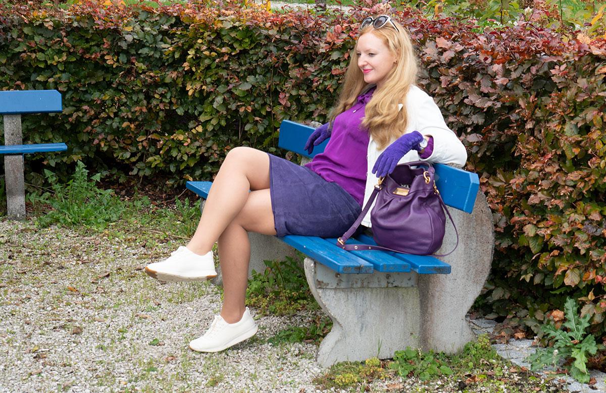 Leder-Outfit-mit-Seidenbluse-und-Merino-Sneakers-auf-bank-sitzend